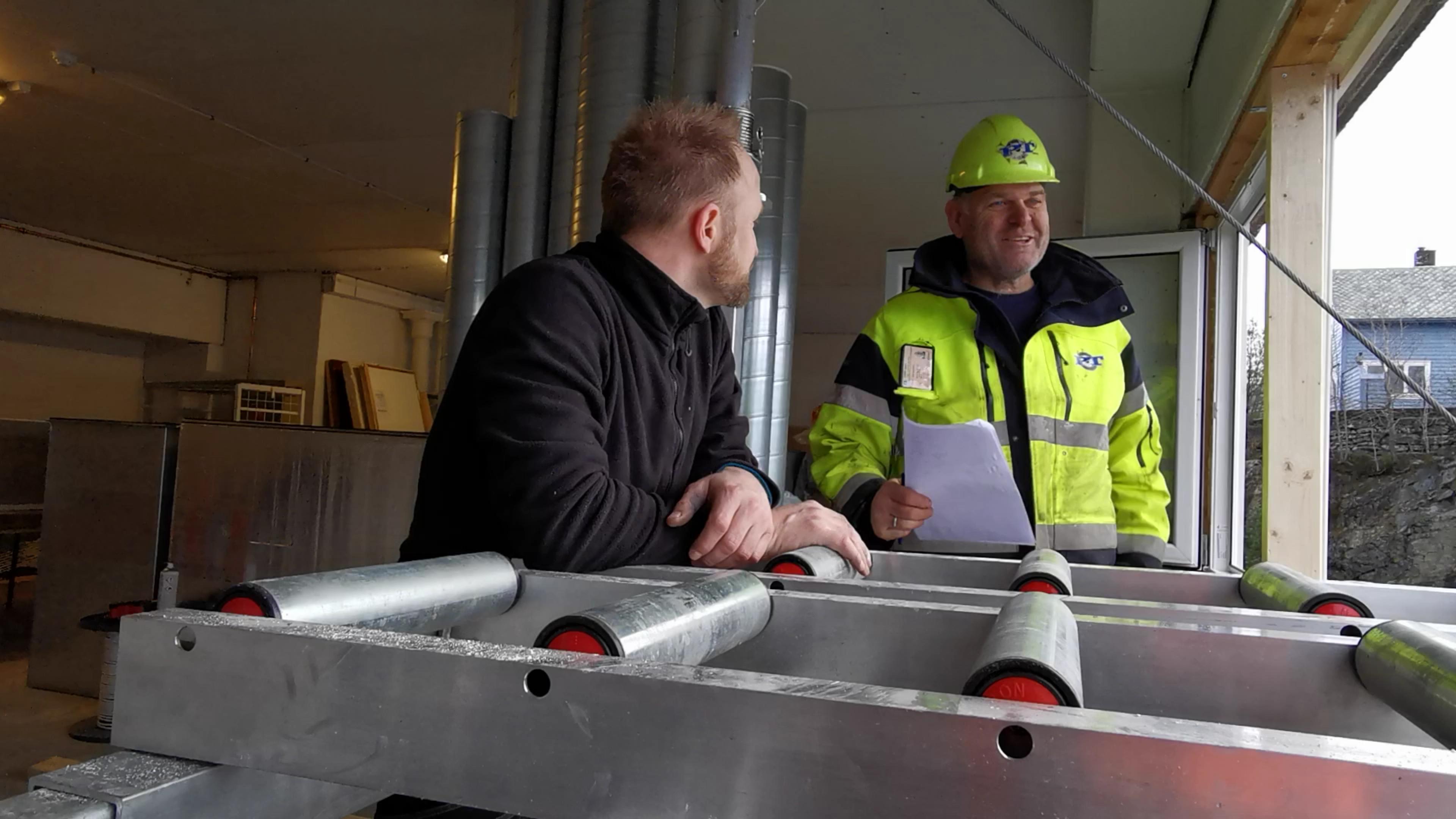 Gründer Ivar Ole Wik står ved rullene til Liftroller Wall, og snakker med kranfører fra Padøy Transport