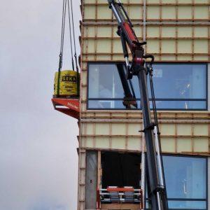 Sekk med byggavfall rulles ut på rullene til Liftroller Wall for så å bli kranet ned