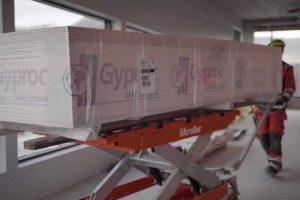 Pakke med gipsplater ligger på rullene til Liftroller Wagon og blir trillet på tildelt plass i bygget