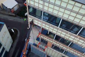 Pakke med gips kranes inn på Liftroller i vindu på byggeprosjektet Kilen